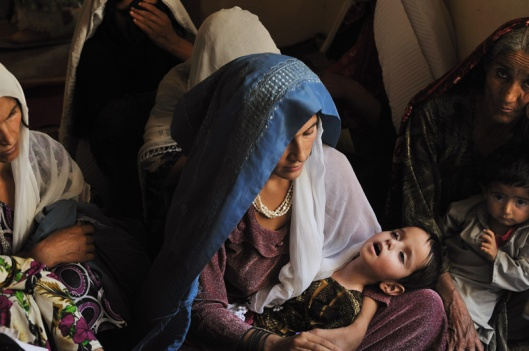 An Afghan woman holds her sick daughter before Dr. Zubeida, a midwife from the mobile health unit funded by the UNFPA, as she inquires about her daughter's condition as, in Charmas Village, a remote area of Badakhshan, Afghanistan. Photo © Lynsey Addario / VII